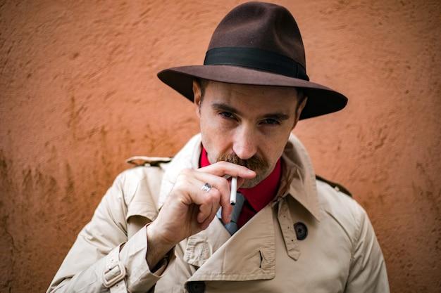Винтажный детектив курит сигарету в трущобах города