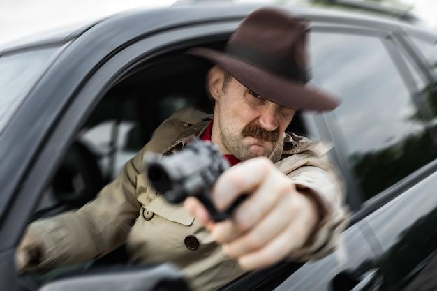 車で犯人を追いかけて銃で銃を狙う探偵
