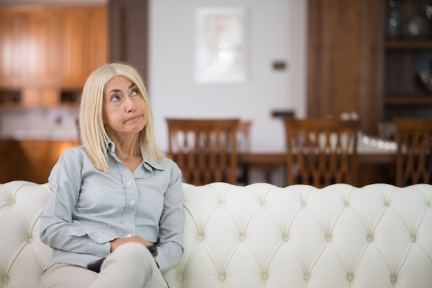 Портрет улыбается женщина, отдыхая на диване в своем доме