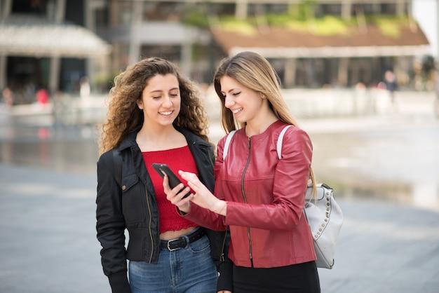 自分の携帯電話を一緒に使用している女性の友達