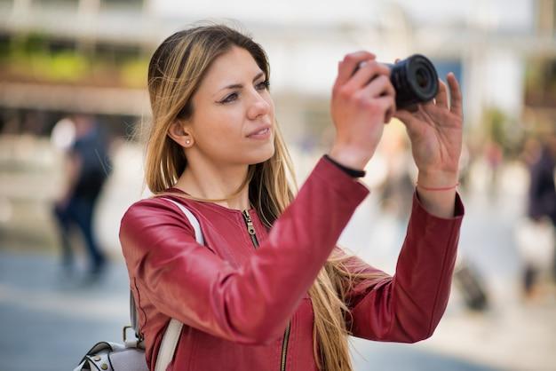 Молодая женщина с помощью беззеркальной камеры