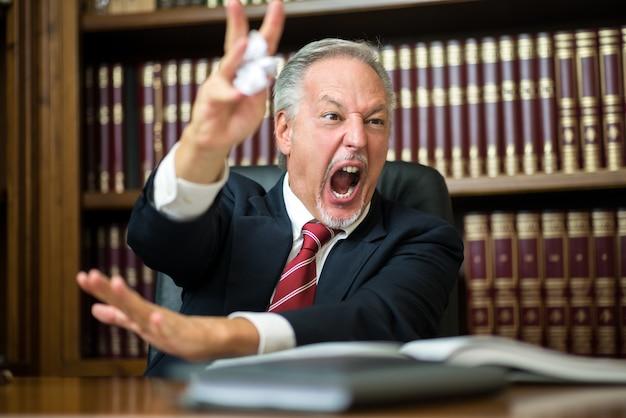 怒っているビジネスの男性がしわくちゃのドキュメントを解き放つ