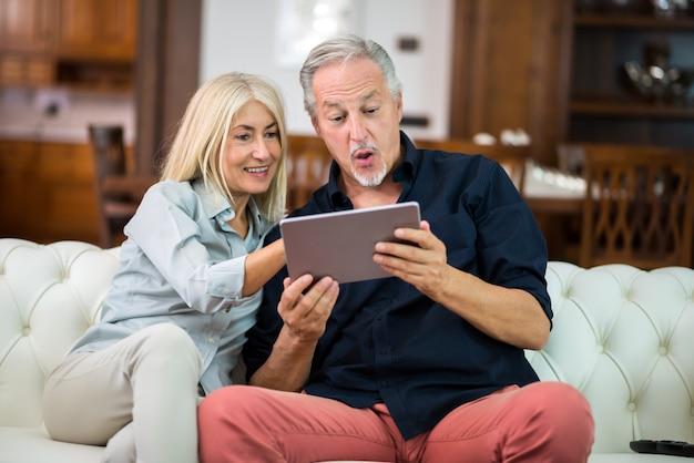 Пожилая пара с помощью цифрового планшета