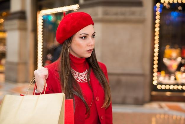 クリスマス前に街で買い物をする若い女性の笑みを浮かべてください。