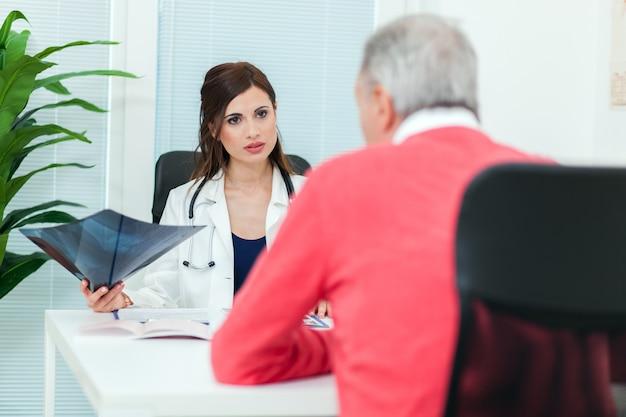 医者は彼女の患者とレントゲン写真を調べる