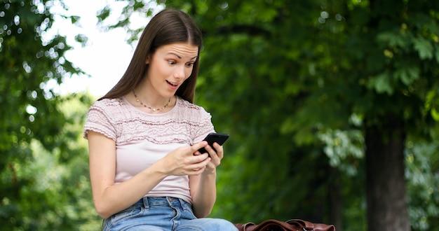 彼女のスマートフォンで良いニュースを読んで非常に幸せな女性