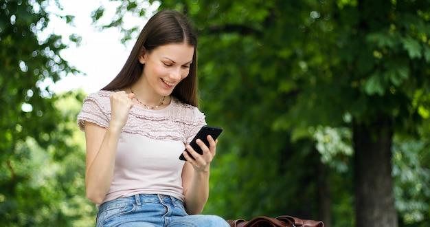 Очень счастливая женщина читает хорошие новости через свой смартфон - концепция победы