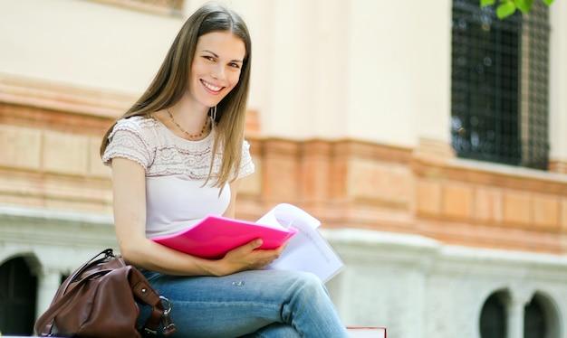 公園で屋外歩行と笑顔を保持している女子学生