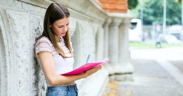 本を読んで笑顔の学生屋外