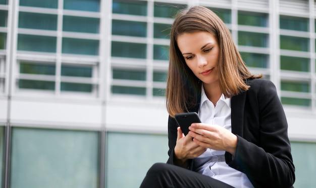 屋外のベンチに座って電話で話している若い女性の肖像画