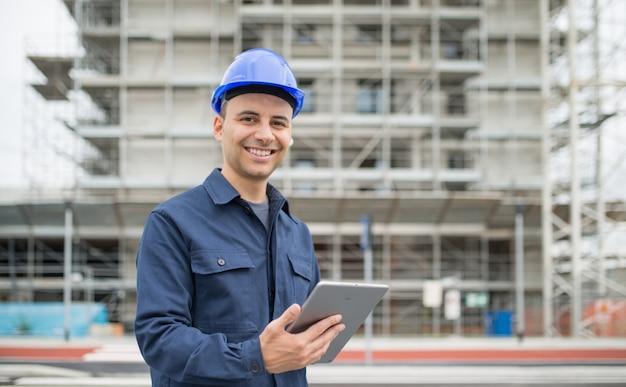 Менеджер сайта с помощью своего планшета перед строительной площадкой