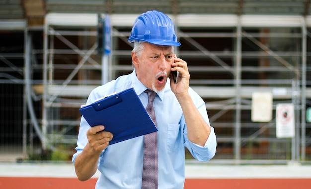 電話で叫んで怒っているシニアエンジニア