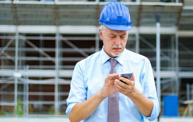 建設現場で屋外の彼のスマートフォンを使用してシニアエンジニア