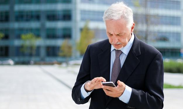 屋外の彼のスマートフォンを使用して成熟した実業家