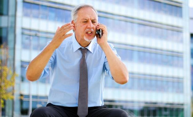 Старший деловой человек кричит на телефон открытый, сидя на скамейке