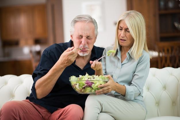 風味のないサラダを味見するカップル