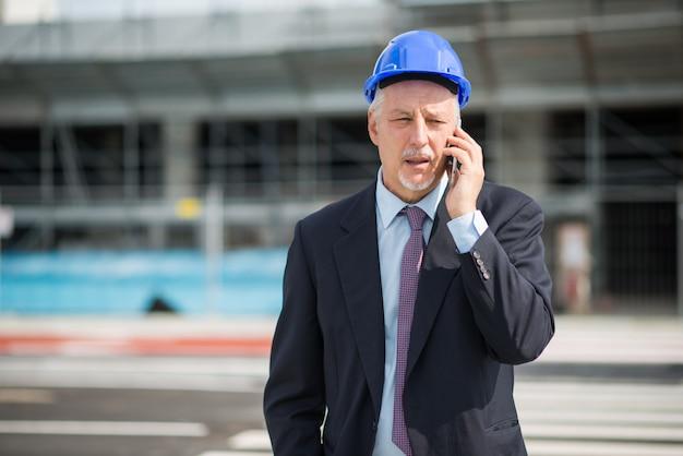 Портрет архитектора разговаривает по телефону со своим подрядчиком