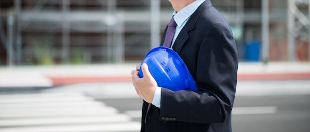 建設現場の前で彼の帽子を保持しているサイトマネージャー