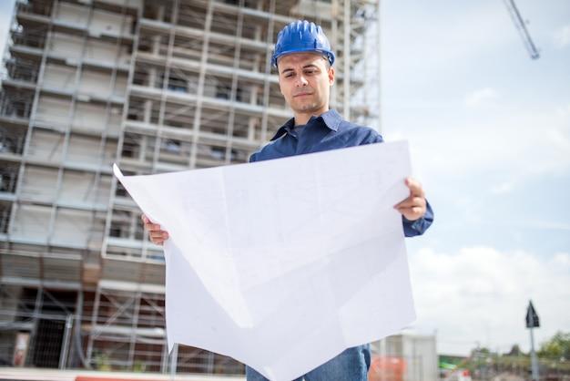 建設現場の前で青写真を読むサイトマネージャー