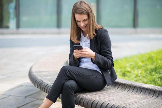 Деловая женщина, используя ее мобильный телефон