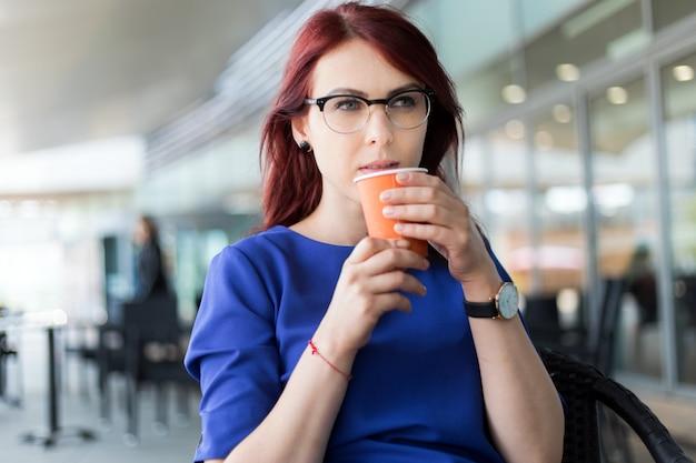 Счастливая задумчивая женщина думает в кафе кафе на улице