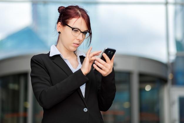 Улыбается бизнесвумен, используя смартфон открытый
