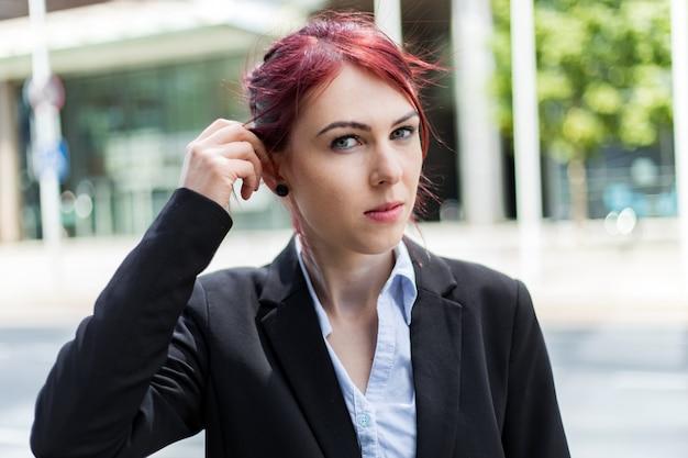 Уверенно молодой женский менеджер на открытом воздухе в современных городских условиях