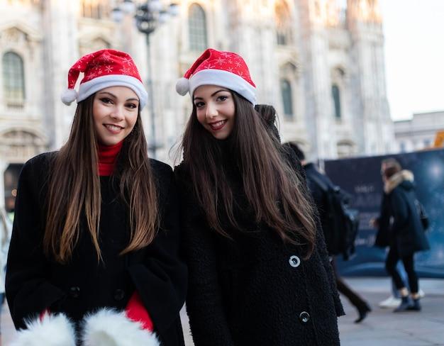 Две милые улыбающиеся молодые женщины делают покупки в милане