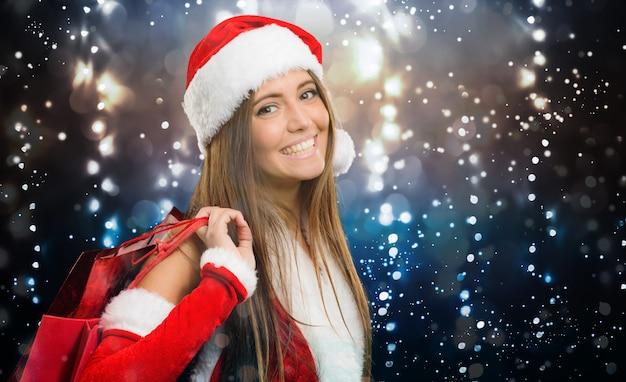 Женский санта-клаус за покупками под снегом