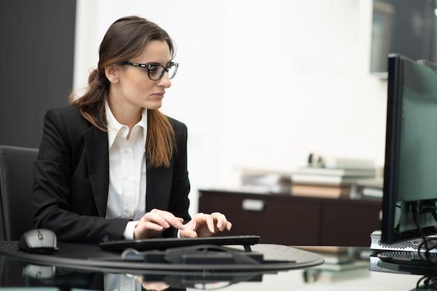 Женщина, используя свой компьютер на работе