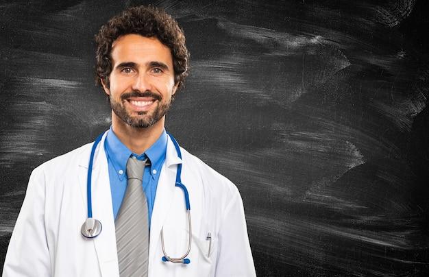 黒板背景に笑顔の医者