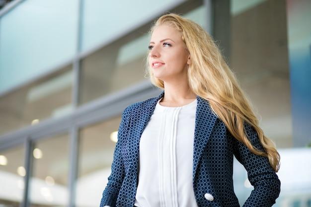 モダンな都会の環境で屋外自信を持って若い女性マネージャー