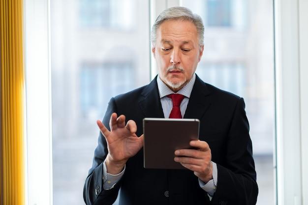 立っていると彼の手でデジタルタブレットを保持している上級ビジネスマン