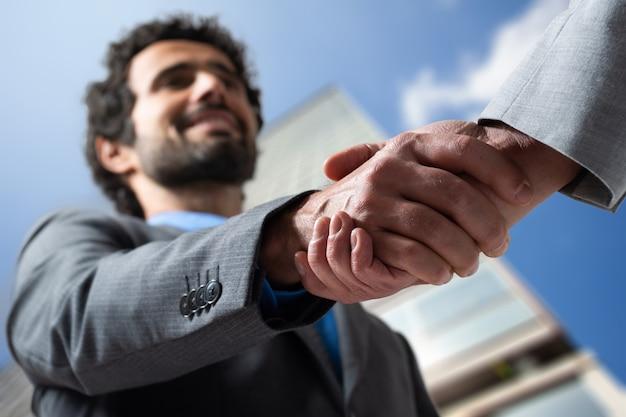 Бизнесмены рукопожатие на открытом воздухе в современной обстановке
