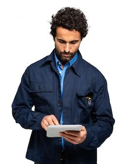Специалист по строительству используя планшет изолированный на белизне
