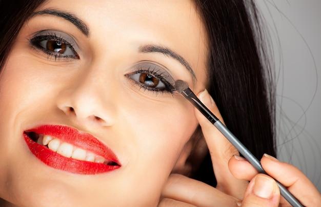 Молодая красивая женщина, применяя подводка для глаз на веко с карандашом