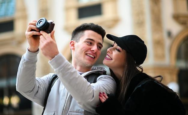 都市で写真を撮るツーリストの若いカップル