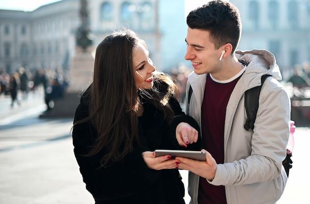 街を訪れながら屋外デジタルタブレットを使用して若いカップル