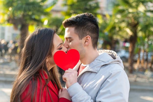 Пара, охватывающая их поцелуй с сердцем