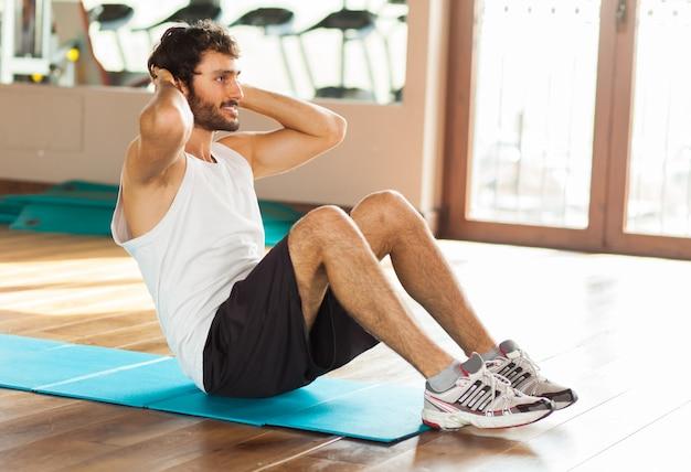 男はジムで彼の腹部の筋肉をトレーニング