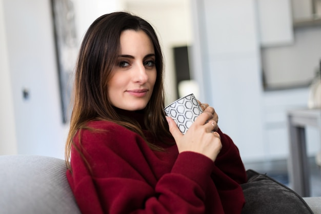 Молодая женщина, имея горячий напиток остроумие на ее диване