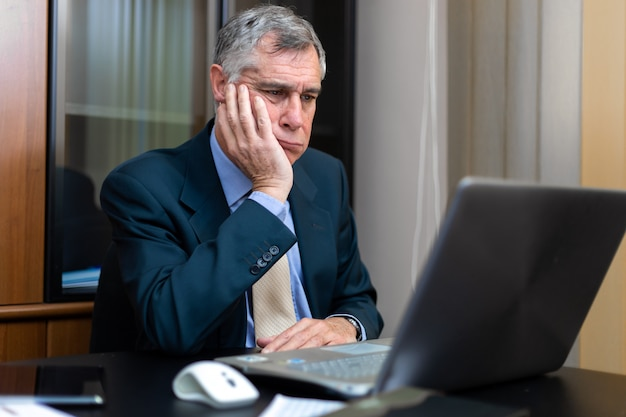 Скучающий бизнесмен перед своим ноутбуком