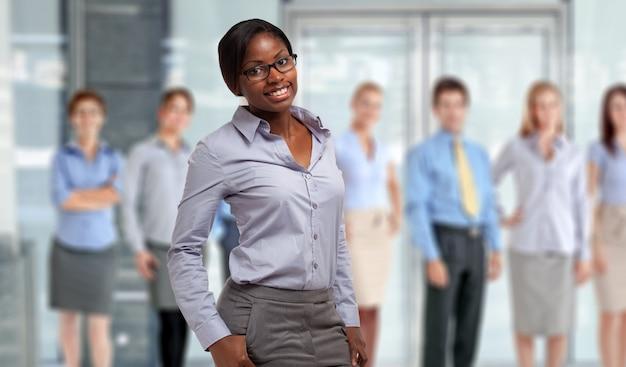 Молодая черная коммерсантка перед группой бизнесменов