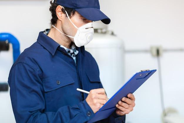 マスク、コロナウイルスの概念を身に着けている職場での配管工