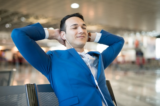 Человек слушает музыку во время ожидания в аэропорту