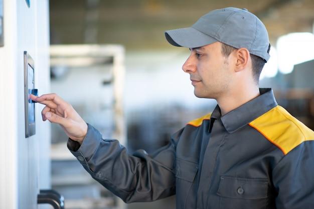 工場でタッチスクリーンを使用する労働者