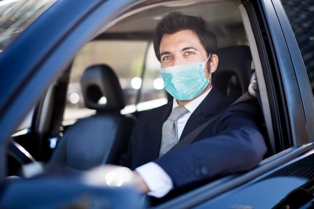 Человек в маске за рулем своего автомобиля