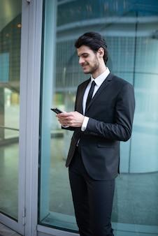 彼の電話でアプリを使用するビジネスマン