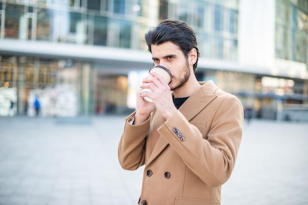 電話で話していると街を歩きながらコーヒーのカップを保持している男