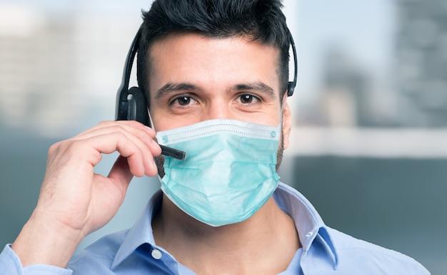 Человек в маске с помощью микрофонной гарнитуры